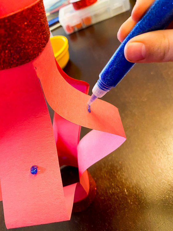 Adding glitter glue to the paper lantern.
