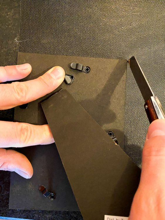 Cutting the screening using the back of the frame as a template.