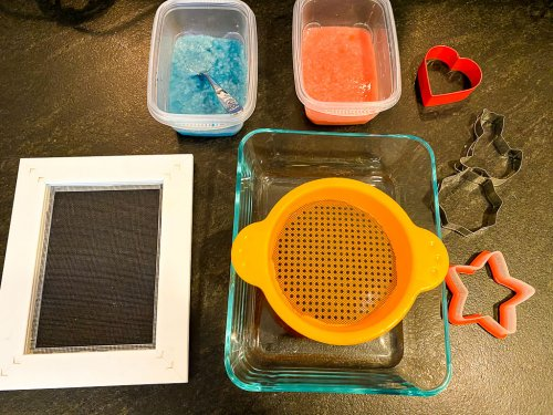 Showing the Chinese paper making supplies with two containers of pulp, cookie cutters, a DIY strainer, a plastic strainer and a glass container.