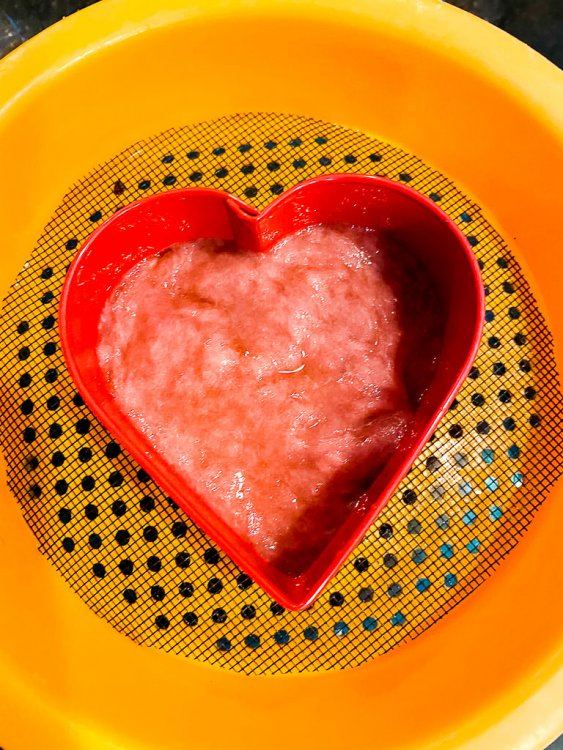 A heart shaped cookie cutter sitting inside the plastic strainer with red pulp.