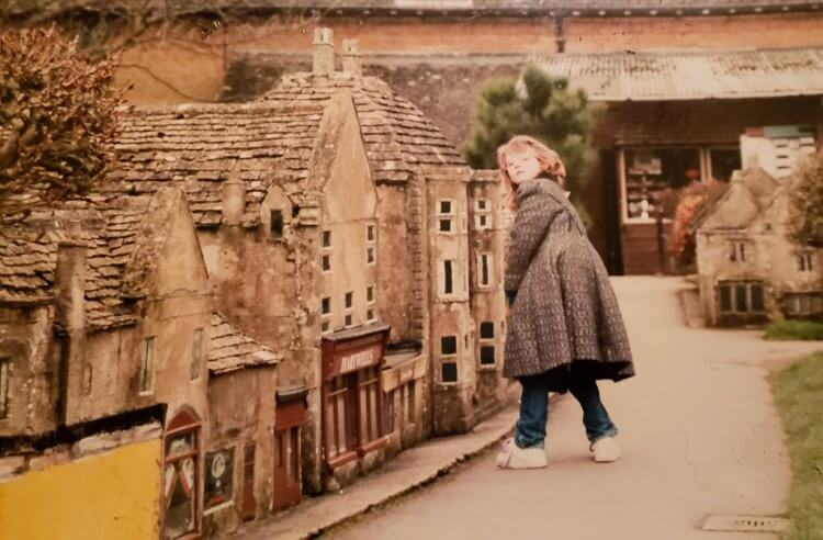 Vintage photo of a little girl standing near a replica village in England.