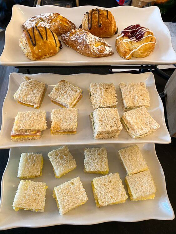 Three tiered platter with tea sandwiches and pastries.