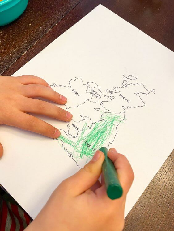 Little boy's hand coloring the map of Great Britain