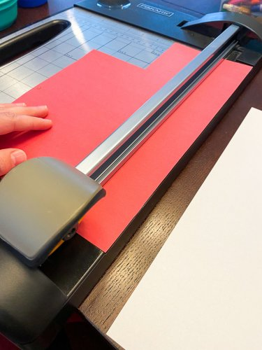 Paper cutter with red paper being cut into strips