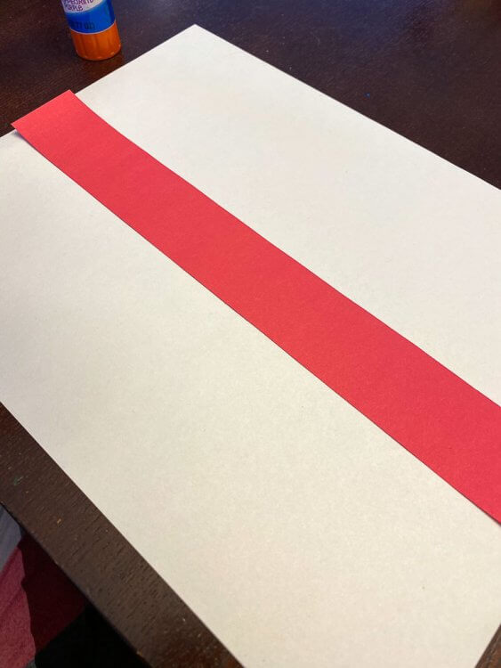 Thin red strip of paper laid over a white sheet of paper to make the flag of England
