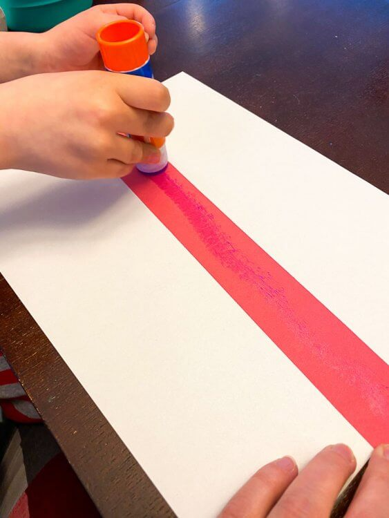 A child's hand gluing a red strip of paper to a white sheet of paper.