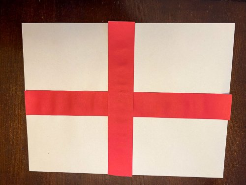 Flag of England with two red stripes forming a cross at the center of a white sheet of paper.