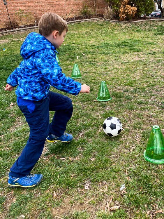 Little boy in an owl coat kicking a soccer ball between to cones.