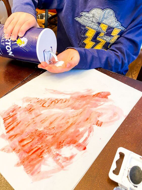 Boy sprinkling salt onto his watercolor painting.