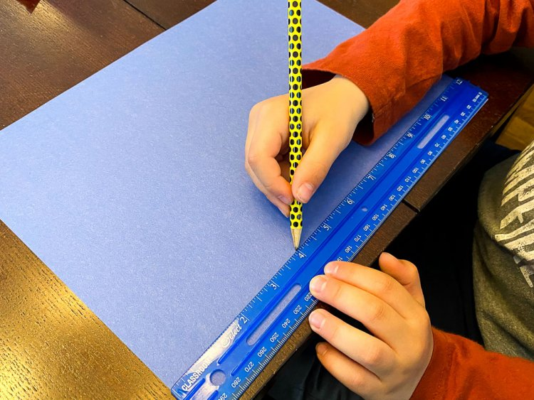 Little boy using a ruler to mark on a blue sheet of paper.
