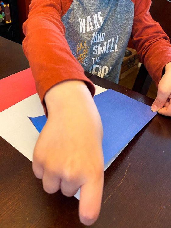 Little boy gluing a piece of blue paper to a piece of white paper.