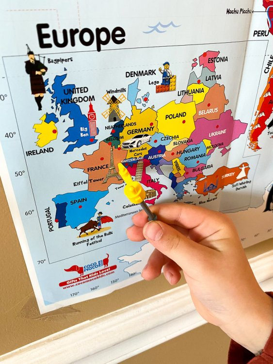 Little boy showing the location of France on the map.