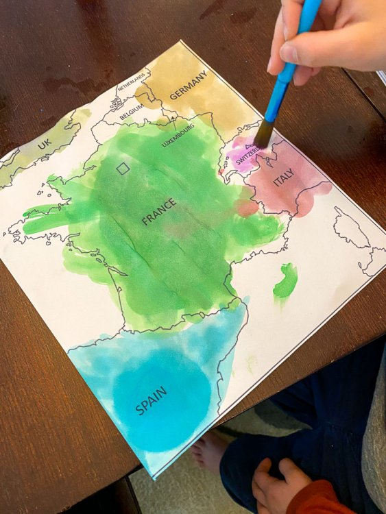 Child coloring the map of France with watercolors. He is coloring Italy Red.