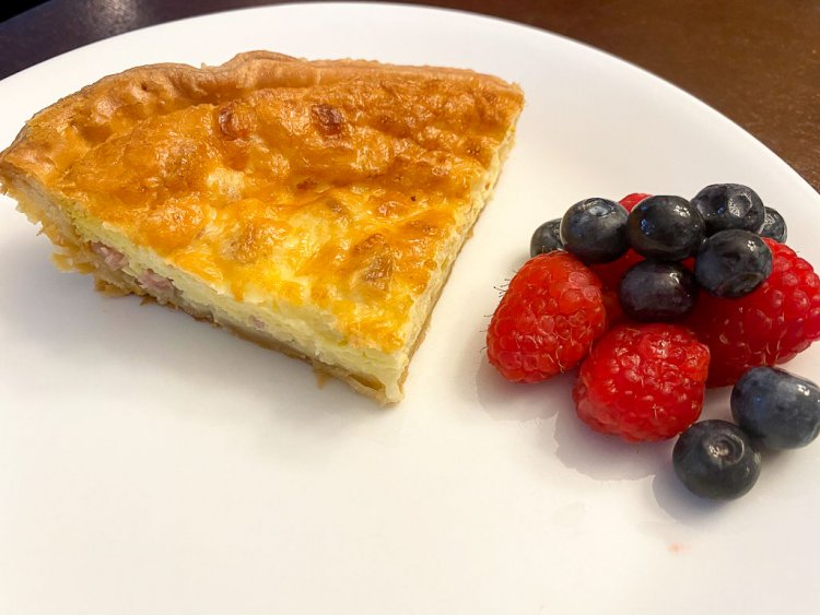 Quiche with fresh berries on a plate.