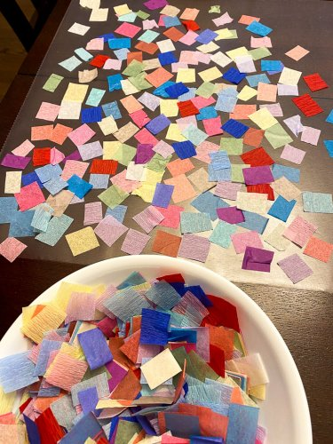 Cut up pieces of tissue paper with contact paper laid out.