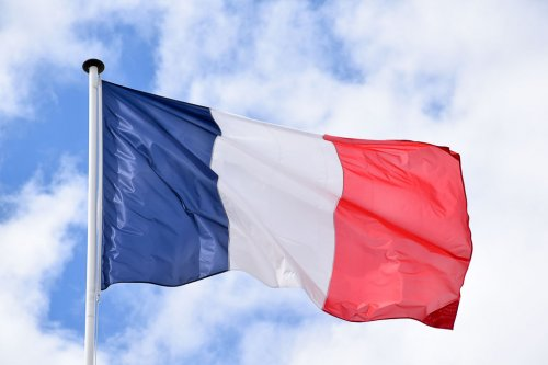 Flag of France flying in the wind with fluffy white clouds behind it.