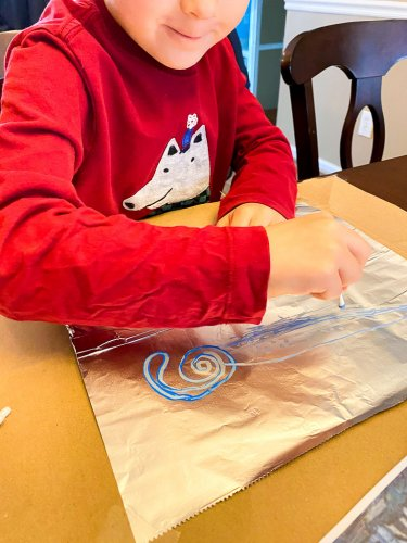 Little boy painting on foil with blue paint using q-tips.