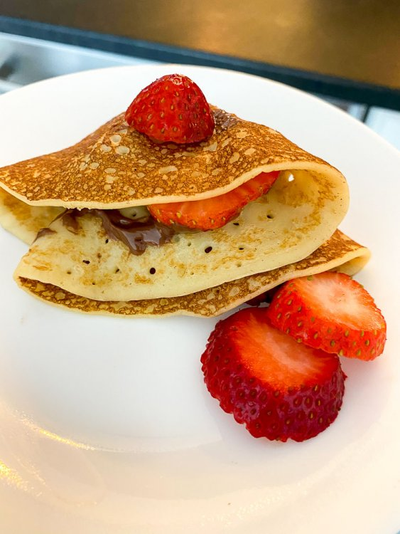 Finished crepe folded on a plate with nutella and strawberries.