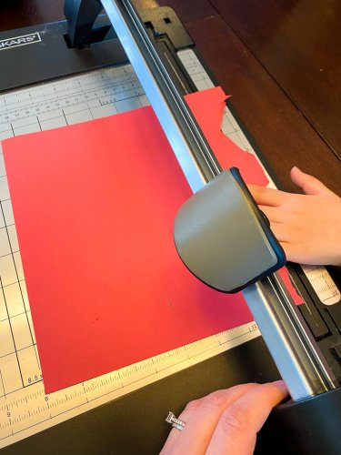 Little boy using a paper cutting machine to cut a piece of red paper.