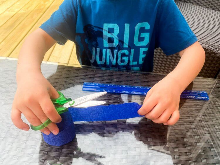 Little boy cutting crepe paper into 12 inch strips.