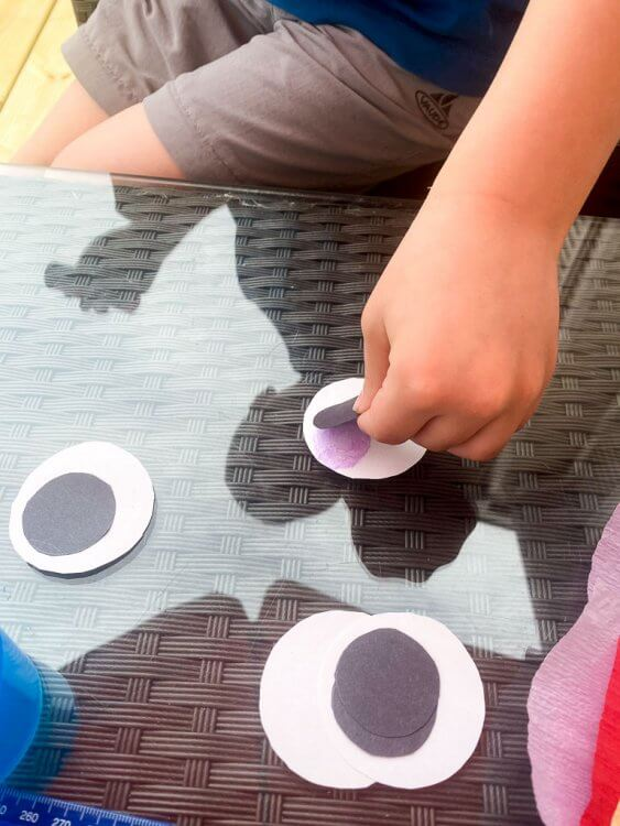 Little boy gluing black dots to white paper circles.