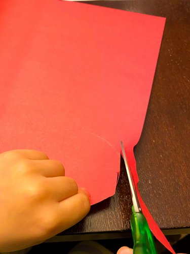 Little boy cutting out circles with scissors on red paper.
