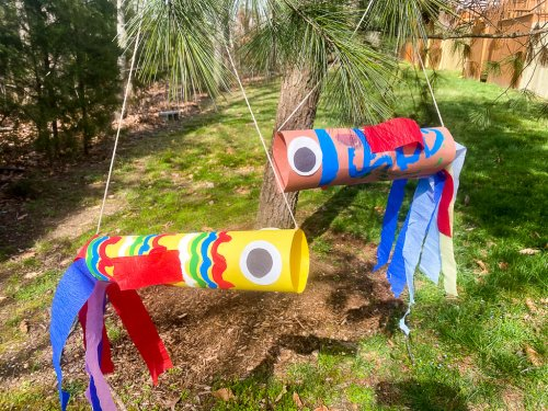 Two finished fish kites hanging from a tree.