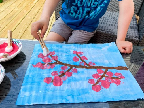 "Adding pink ""blossoms"" onto the branch using the cotton balls."
