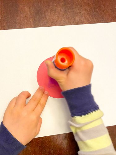 Little boys hand gluing a red circle onto a white sheet of paper.
