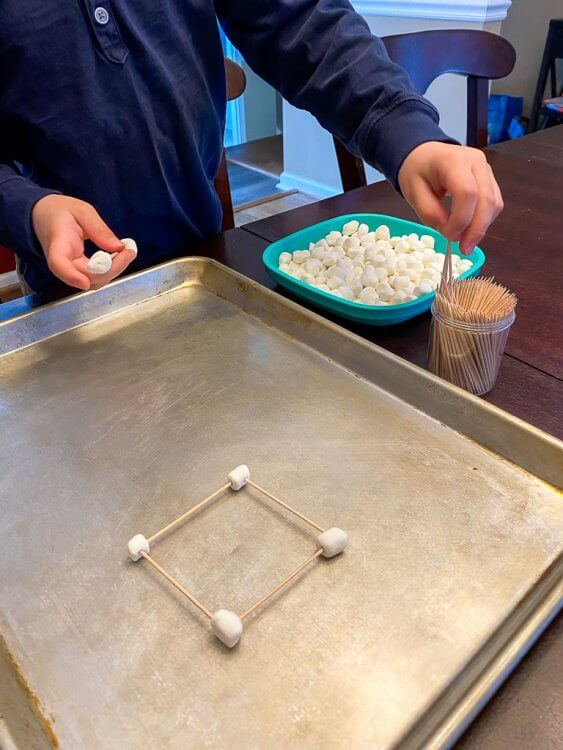 Building with marshmallows and toothpicks on a cookie sheet.