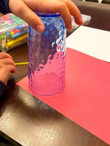 Boy using a upside down cup to trace circles on red paper.
