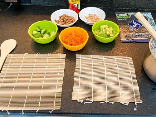 Supplies to make sushi: bamboo mats, cut up foods.