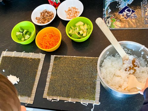 Picture of preparation to make sushi with kids: bamboo mats with one layer of seaweed, pot with white rice, cut up foods to put inside the sushi.