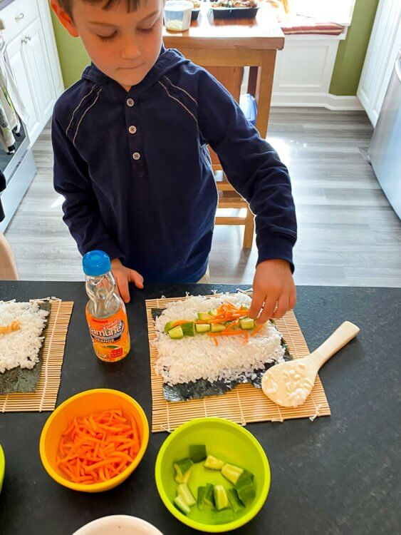 Little boy adding carrots, avocado and cucumbers onto his sushi roll.