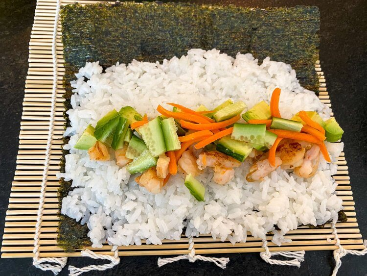 Sushi with white rice and a mix of vegetables laying on a seaweed sheet over a bamboo mat.