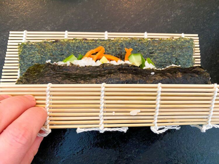 Rolling up the sushi using a bamboo mat.