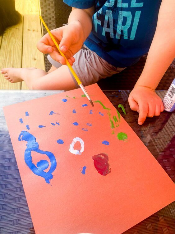 Little boy painting blue, green and white dots on orange paper to make a Japanese fish kite.