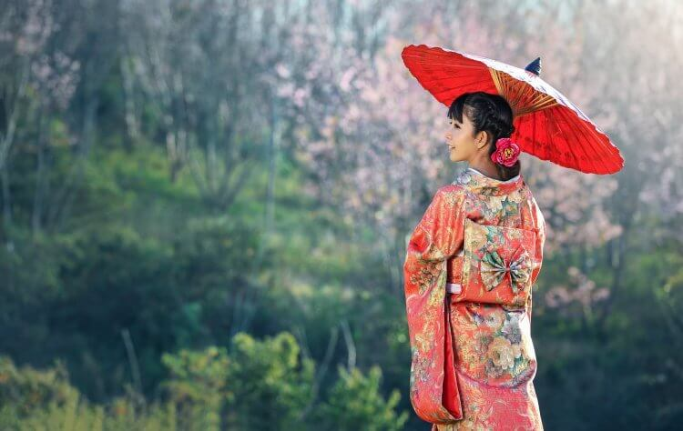 Japanese woman wearing the traditional dress with a red umbrella looking into the distance.