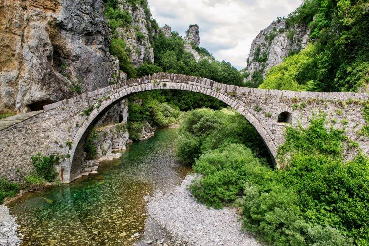 Photos of a bridge in modern day Greece. The bridge is over a river with lush green and high mountains.