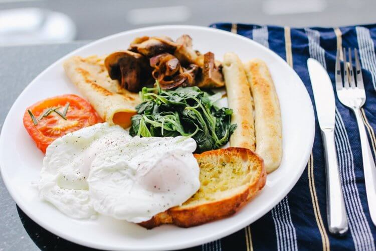 Traditional English breakfast with eggs, toast, tomatoes and meat.