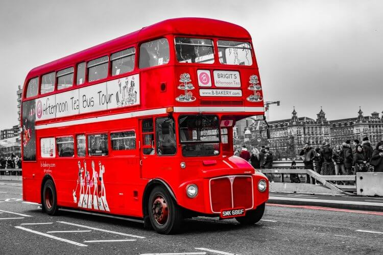 Double decker red bus driving on the streets of London.