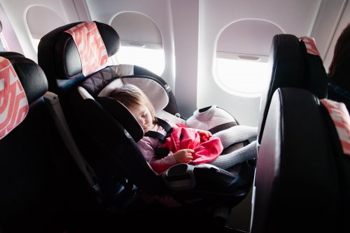 Little girl asleep in her car seat on an airplane.