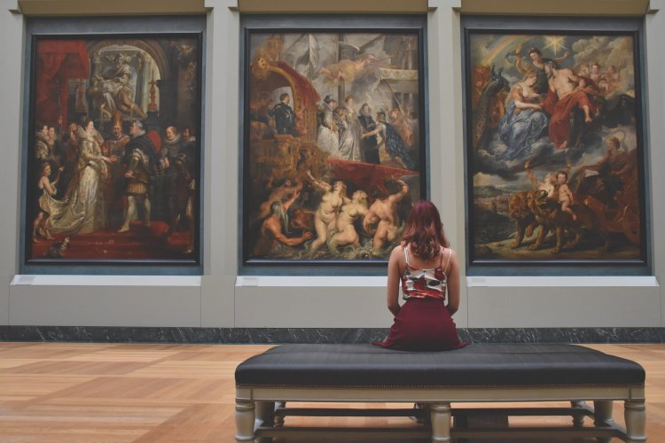 Woman sitting looking at art in a gallery.