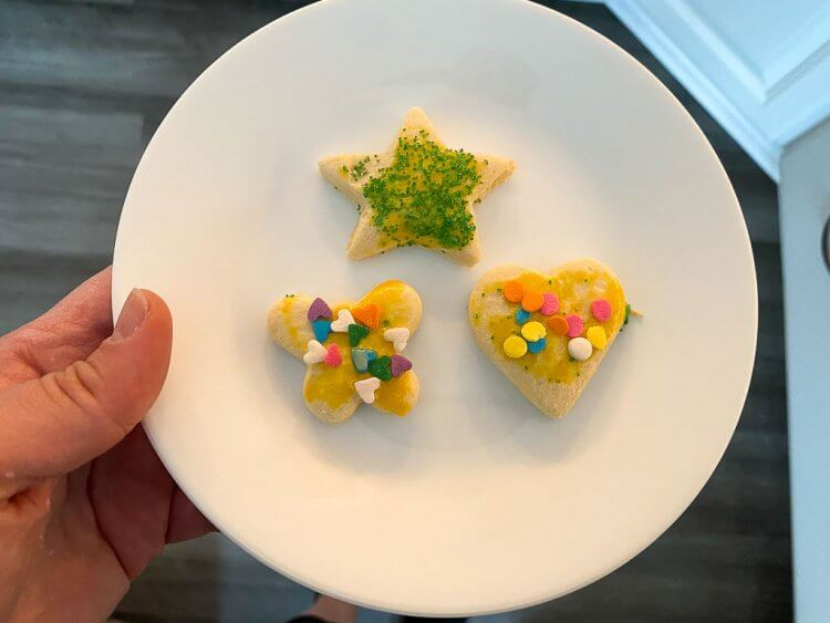 Three little cookies with sprinkles in the shape of a butterfly, heart and star.