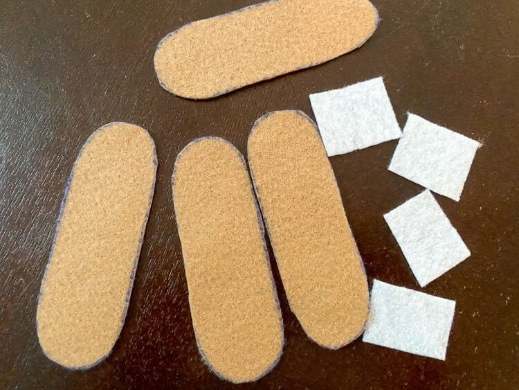 Cut out band aids with white squares getting ready to be sewn.
