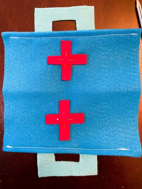 Pinning the red crosses to the fabric pouch.