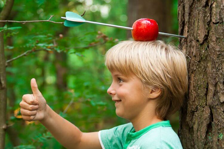 Little boy with an apple on his head. The apple has a arrow through it. William Tell.