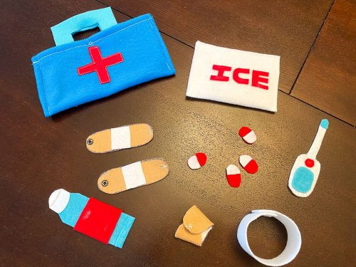 Completed felt first aid kit with ice pack, band aids, pills, bandages and thermometer.