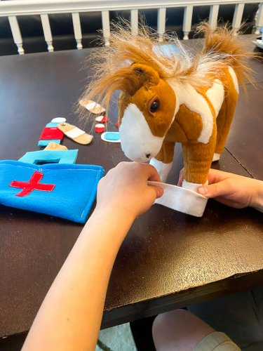 Little boy bandaging his stuffed horses foot with the medical kit.