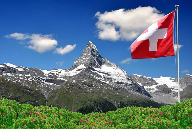 Matterhorn in the distance with a swiss flag in the foreground.